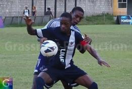 JC's captain Junior Flemmings shield off Kingston College defender Romar Beckford.